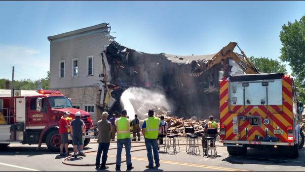 Firefighters sprayed water on the wreckage to knock down dust and douse any hot spots as a backhoe exposed the interior of Leebo's Bar & Grill in downtown Gilmanton. Due to the nature of the fire early Thursday, June 6, authorities said the building had to be torn down.