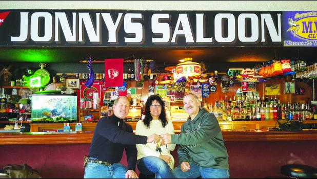 Jonny Marshman (right) recently handed the keys of Jonny's Saloon over to Kimball Strickland, (left) new owner of Jonny's.  Pictured with the two is Kristine Bowman, girlfriend of Kimball who will also be helping at the bar.  Photo by Cheryl Nymann