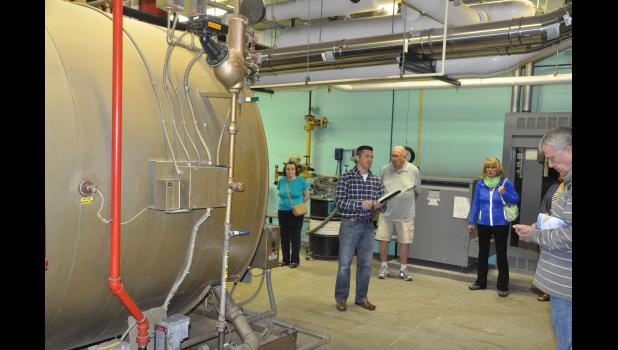 Luke Schultz, a facilities management expert with CESA 10, explained the various functions of mechanical equipment in the Mondovi Schools' basement during a public facilities walk-through on May 10. Many components, including a massive steam boiler from 1972 (left) have reached the end of their life expectancy and are inefficient.