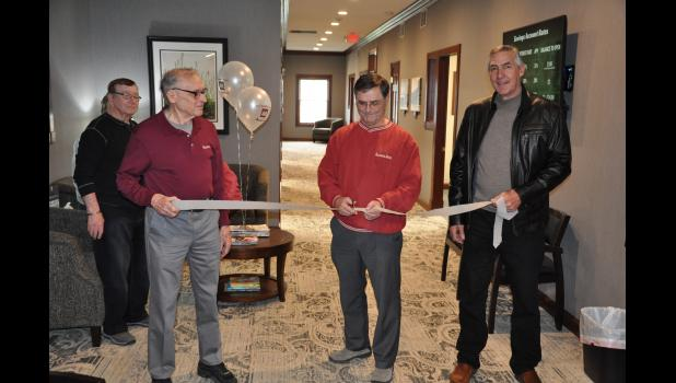 Frank Servais, President of Alliance Bank, cut a ribbon held by bank Board of Directors members Gary Schlosstein (left) and Dan Heike (right) during an open house event on Thursday, April 20, to showcase the new addition (background) and other updated amenities at Alliance Bank's Mondovi branch.