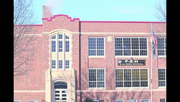 PEM State wrestlers and coaches smile for a photo in the Xcel Energy Center after a long weekend full of wrestling on Saturday, March 3. Photo by  Barb Marx