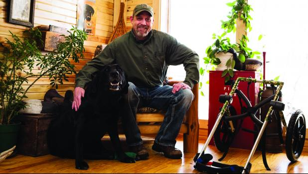 Jason Parker poses alongside his black lab Gunnar and the chair that Gunnar uses to get around. Similar chairs are sent to animals all across the country who are in need of one as part of Gunnar's Wheels Foundation.