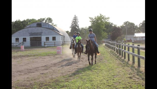 Josephine Stellar, Brett Tomlinson, and Rachel Seifert ride around the show ring at the Pepin County Fairgrounds to warm up their horses for the last practice session July 17. The youth are three of eight who will be showing horses at this weekend's Pepin County Fair.