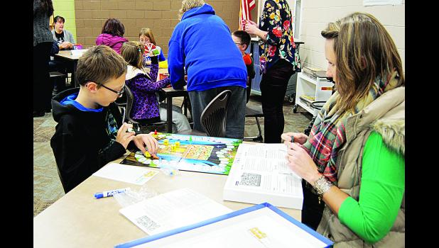 Dane and Nancy play a literacy-related game on Family Literacy Game night. This event took place at Caddie Woodlawn Elementary School on Monday, November 14.  Laura Berndt photo