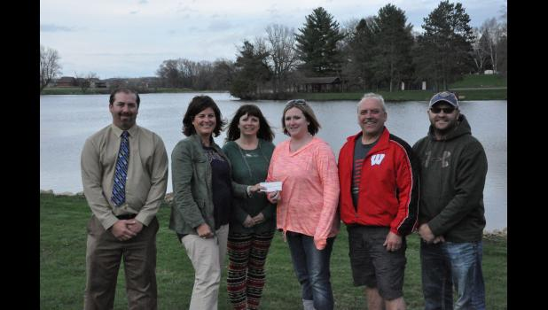 """The Mondovi Board of Park Commissioners accepted a $10,000 check on Tuesday, April 18, from the Mondovi Business Association, derived from the proceeds of the second annual """"Shamrock Shuffle"""" event. Pictured, left to right, are Mondovi Mayor Treig Pronschinske, MBA president Ali Rud, MBA treasurer Bobby Lubinsky, and Park Board members Jenna Fink, Karl Zacharias and Branden Rud. City leaders hope the donation serves as a springboard to action on proposed improvements for Mirror Lake Park."""