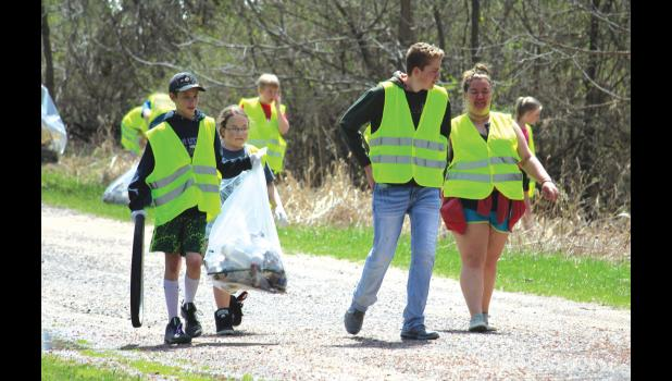 Augusta students walk around the city picking up trash on the road as part of a way to give back to the community during their Hugs for Humanity event on Friday, May 4.
