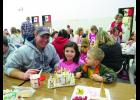 Families and students came together on Wednesday, December 21st to make Gingerbread Houses with tasty frosting, graham crackers and lots of sweets for decorations.  Ava McCoy, her dad and brother enjoying the tasty tradition.  Photos by Carol Boynton