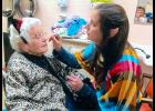 UWEC and volunteer Tabitha Radtke applies resident Audrey Hepper with festive face paint.