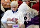 Bev Nisbit reaches for a card to play at the first Community 500 Card Party on Sunday.