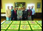 The first place quilt is a queen-sized Kaleidoscope quilt. Women pictured in the photo from left to right are Marie Undeberg, Marilyn Shea, Joan Allen, Dee Delaney, Laurie Meyer, Marcy Swan, Jo Sawyer, Claryce Bany, Marguerite Uthke, and Ladonna Corbin. Not all members are pictured.