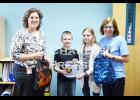 Above, from left to right, are local Ready Set School Board Member Theresa Nunemacher, students Coben Reps and Hannah Fynboh, and Ready Set School Director Karen Sullivan. Theresa and Karen are holding backpacks that will go to St. Charles students in need of school supplies, and, Coben and Hannah are holding a tin that can be filled with donations for the Ready Set School program. Photo by St. Charles Press Editor Laura Berndt.
